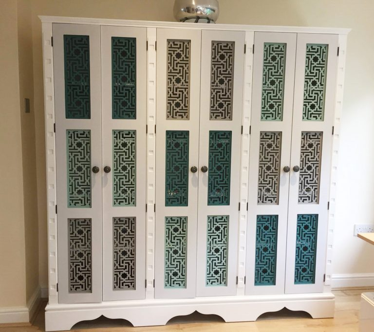 Three sectioned cupboard with vari-toned fretwork panels
