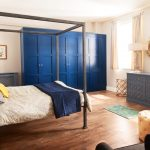 Light, Spacious Room featuring a Grey Radiator Cover and Soft Close Drawers Alongside a Bold Blue Wardrobe