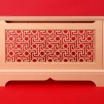 Ethnic radiator cabinet on red wall