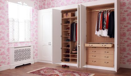 White top coat decorative shutters above a radiator cover, with a large white wardrobe with oak interior