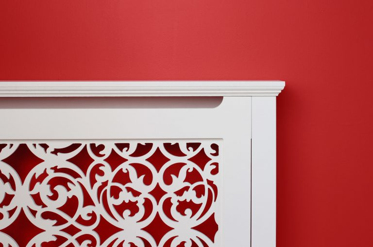 Ornate radiator cabinet on red wall